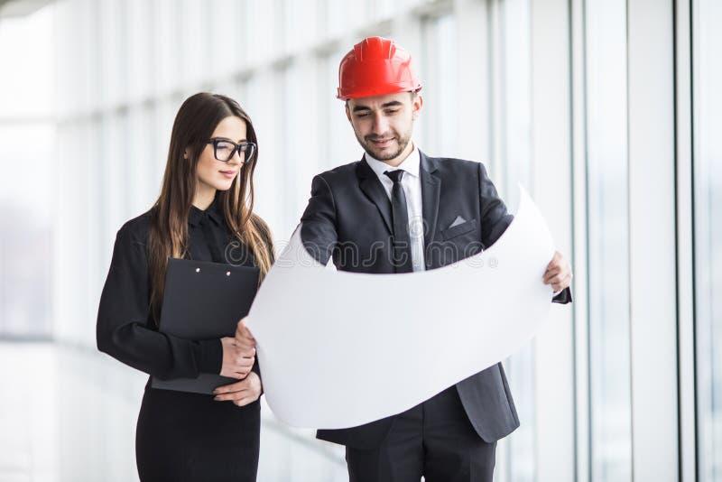 Een aantrekkelijke man en vrouwen commerciële team werkende bouw op het bouwterrein dichtbij panoramische vensters royalty-vrije stock afbeelding