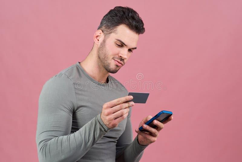 Een aantrekkelijke mens van atletische bouwstijl in een grijze strakke t-shirt houdt een smartphone en een Bankcreditcard Het con stock afbeelding