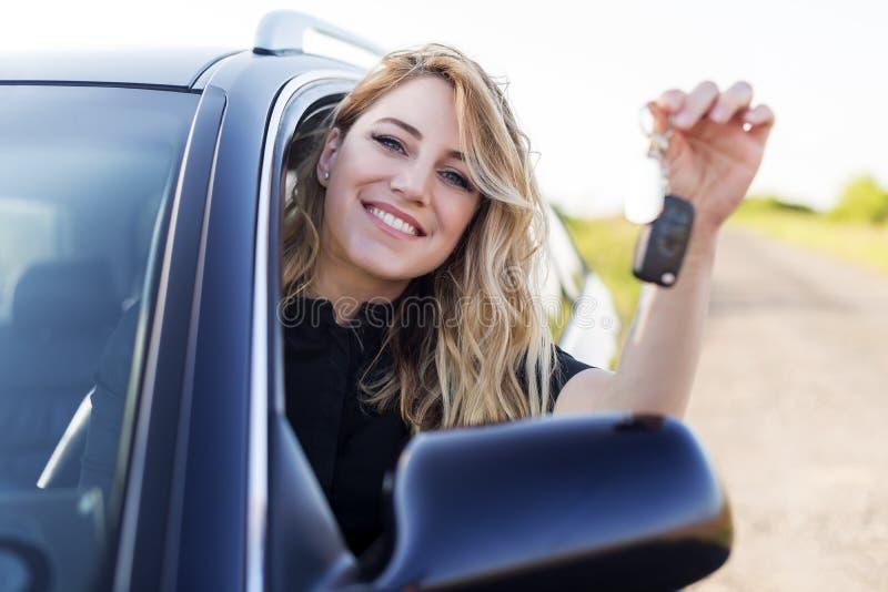 Een aantrekkelijke vrouw in een auto houdt een autosleutel in haar hand stock fotografie