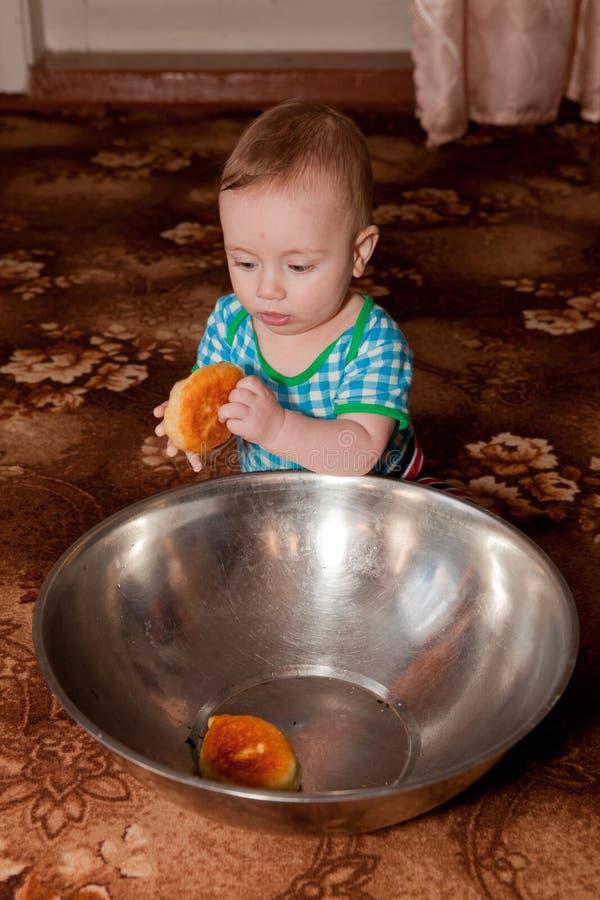 Een aardige jongen die een doughnut van een grote kom eet royalty-vrije stock afbeelding