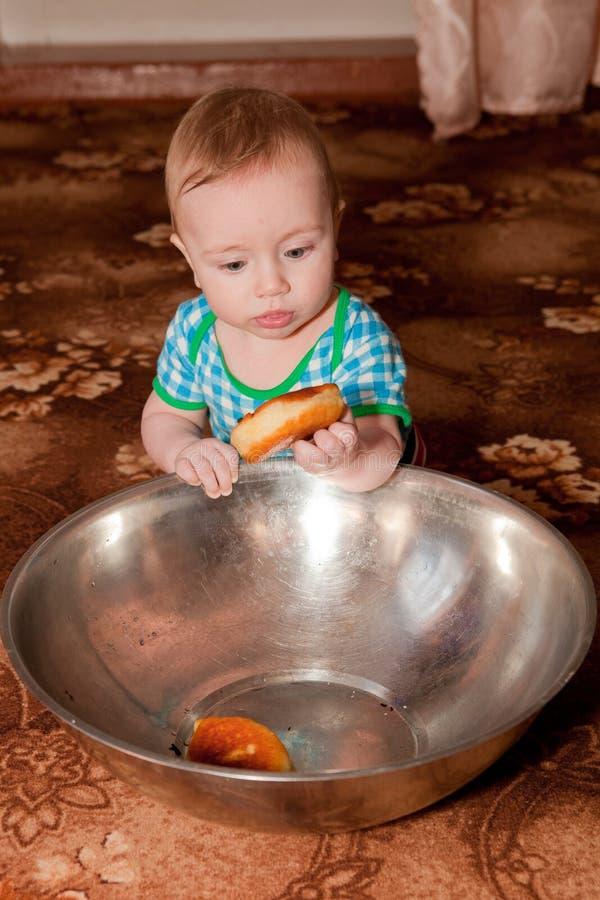 Een aardige kerel die een doughnut van een grote kom eet royalty-vrije stock foto's