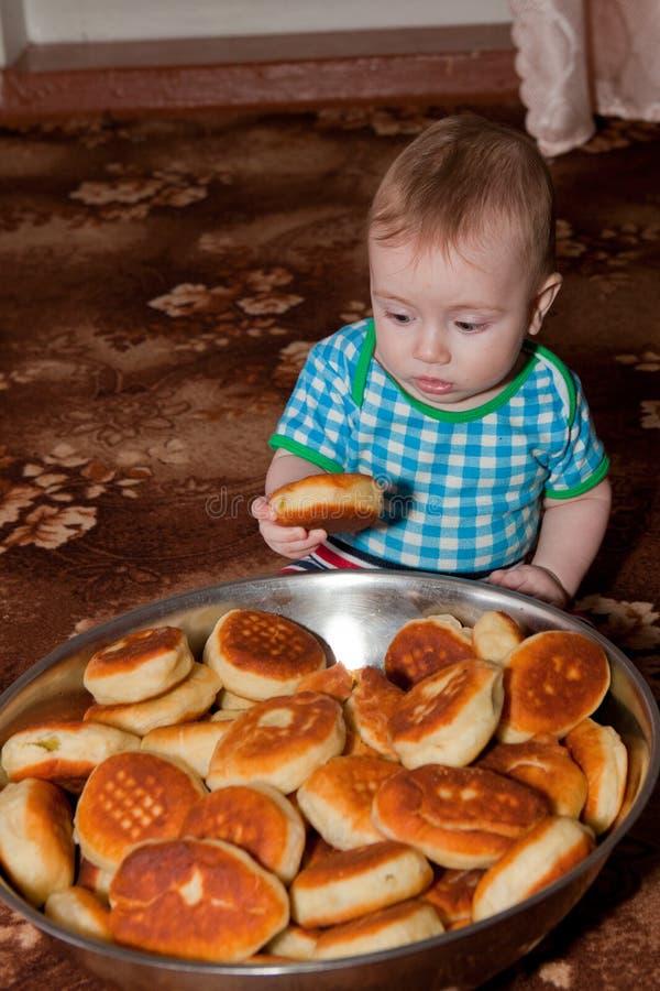 Een aardige kerel die een doughnut van een grote kom eet stock afbeelding