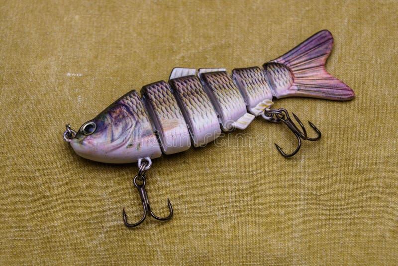 Een aas voor visserij op een geteerd zeildoekachtergrond Samenstelling die wobbler vissen royalty-vrije stock afbeelding