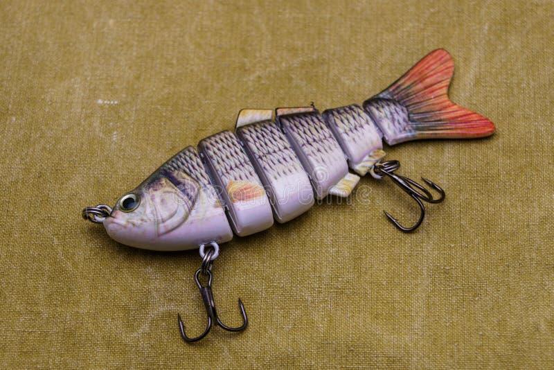 Een aas voor visserij op een geteerd zeildoekachtergrond Samenstelling die wobbler vissen royalty-vrije stock foto