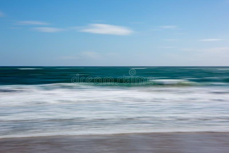 Een abstracte motie vertroebelde strandachtergrond met zandwater en stock foto's