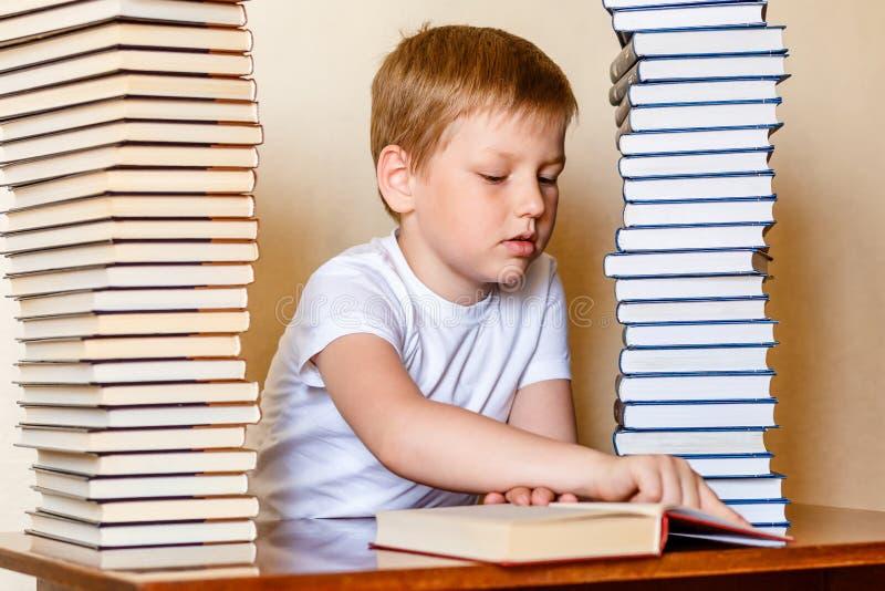 Een acht-jaar-oude jongen leest een boek, die een lijn met zijn vinger vinden het kind leert te lezen stock foto's