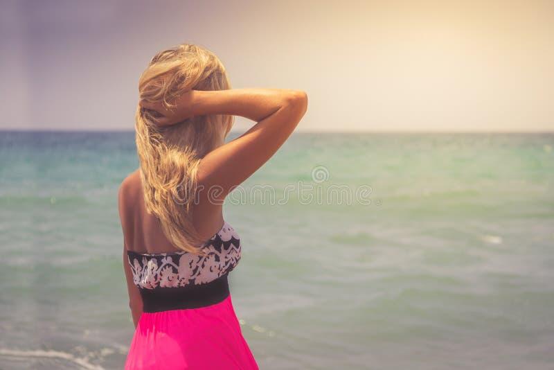 Een achterkantmening over het prachtige jonge vrouw letten op aan overzees en het opheffen van haar handen op zonsopgang royalty-vrije stock afbeelding