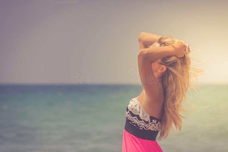 Een achterkantmening over het prachtige jonge vrouw letten op aan overzees en het opheffen van haar handen op zonsopgang royalty-vrije stock foto's
