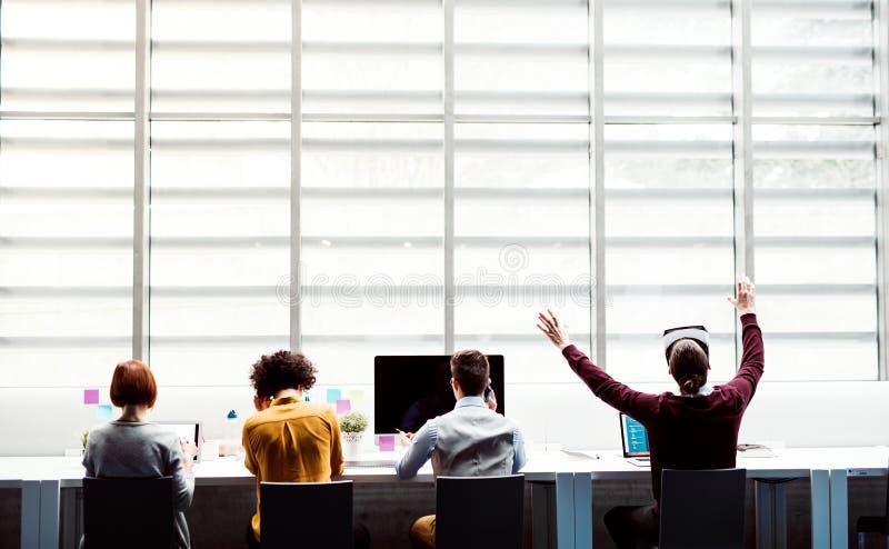 Een achtermening van groep jong zakenlui met VR-beschermende brillen die in bureau werken royalty-vrije stock afbeelding