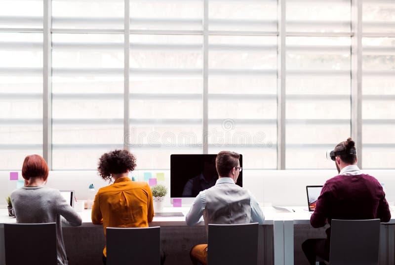 Een achtermening van groep jong zakenlui met VR-beschermende brillen die in bureau werken stock afbeelding
