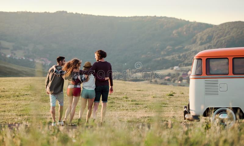 Een achtermening van groep jonge vrienden op een roadtrip door platteland, het lopen royalty-vrije stock afbeeldingen