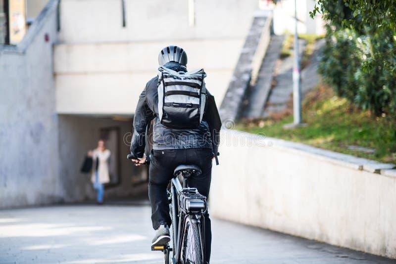 Een achtermening van mannelijke fietskoerier die pakketten in stad leveren De ruimte van het exemplaar stock foto