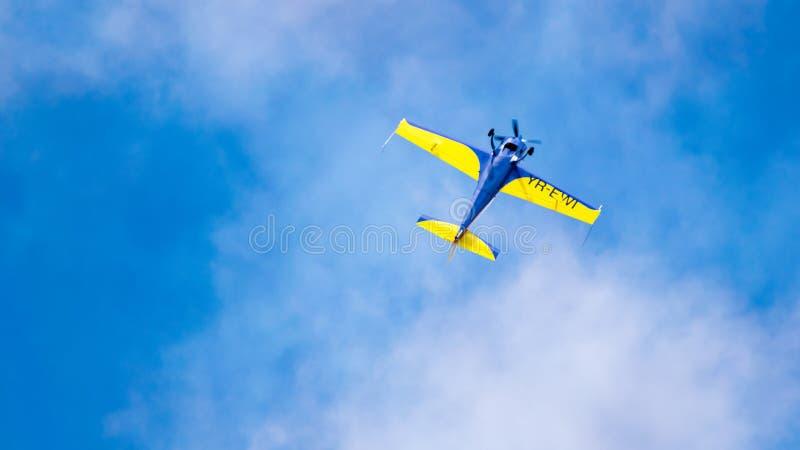 Een acrobatisch vliegtuig, die in de blauwe hemel met witte wolken vliegen, die acrobatiek doen stock foto