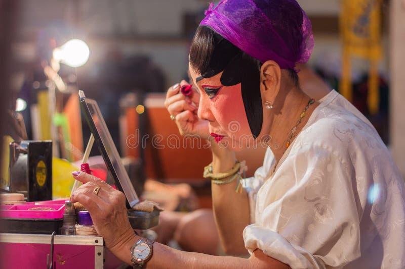Een actrice van het Chinese operagroep schilderen maskeert en het zetten van make-up op haar gezicht vóór het culturele performan royalty-vrije stock afbeelding
