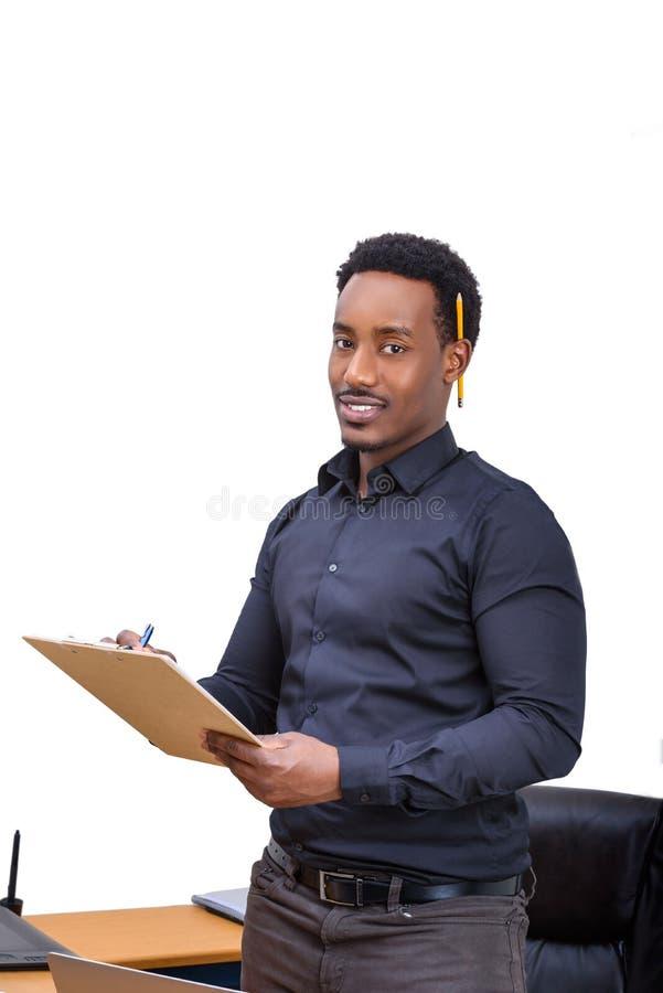 Een Afrikaanse Amerikaanse Bedrijfsmens die en zich op een klembord bevinden schrijven royalty-vrije stock foto's