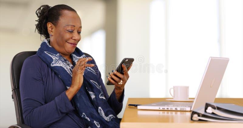Een Afrikaanse Amerikaanse onderneemster gebruikt haar mobiele telefoon bij haar bureau royalty-vrije stock fotografie