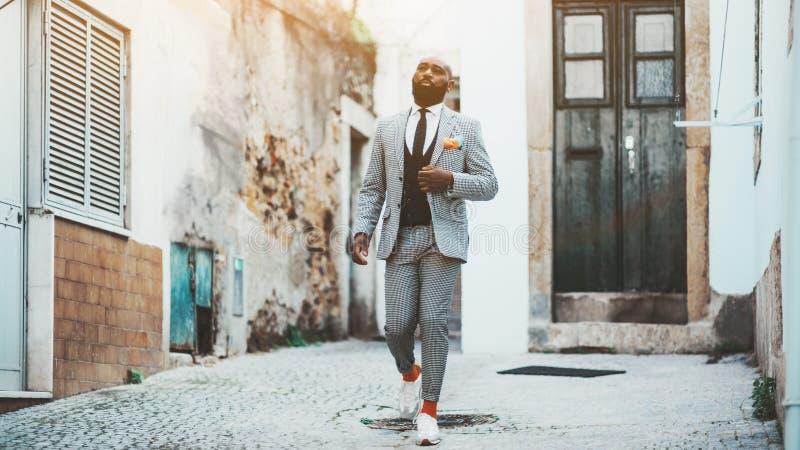 Een Afro-kerel die onderaan de straat lopen stock afbeeldingen