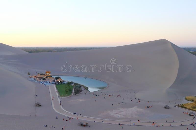 Een afstandsmening van Crescent Lake door Echoing-Sand Mountain Mingsha wordt omringd die stock fotografie