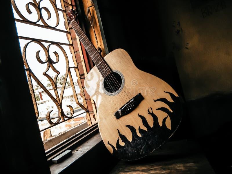 Een akoestische gitaar, geplaatst naast het oude wijnraam, met zacht zonlicht afkomstig van Nostalgia guitar chords Zomermelodie royalty-vrije stock foto's