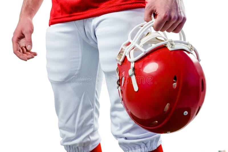 Een Amerikaanse voetbalster die zijn helm op haar hand nemen royalty-vrije stock afbeelding