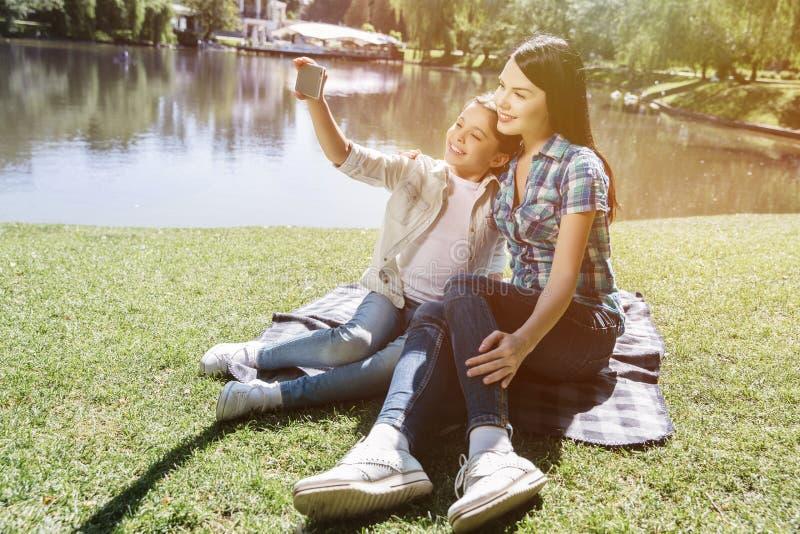 Een ander beeld van kleine familiezitting samen en stellend op camera Het kleine meisje houdt telefoon en neemt selfie stock afbeelding