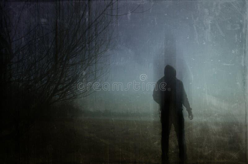 Een angstaanjagend silhouet van een eenzaam cijfer met een kap op een gebied op een de wintersnacht Met een donkere, griezelige v stock foto