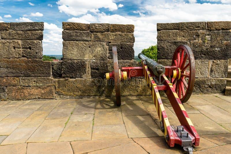 Een antiek kanon in rood-gele kleur op de muren van een middeleeuws kasteel royalty-vrije stock foto's