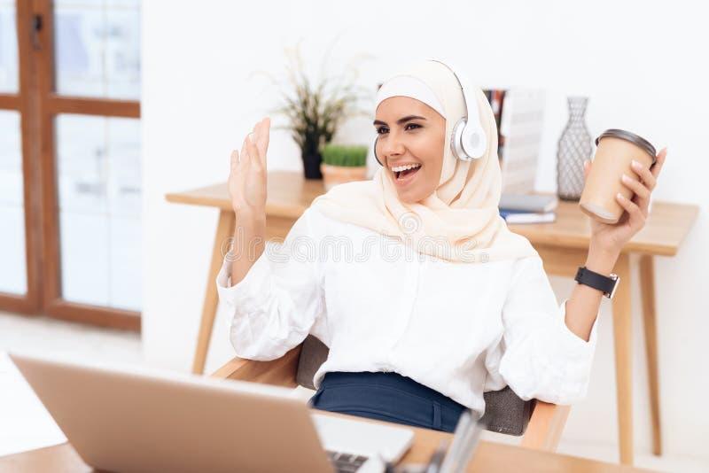 Een Arabische vrouw in hijab luistert aan muziek op hoofdtelefoons royalty-vrije stock foto