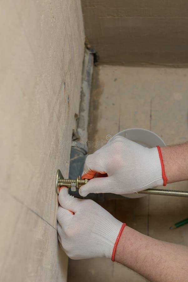 Een arbeider bevestigt omhoog een muur van bouten stock afbeeldingen