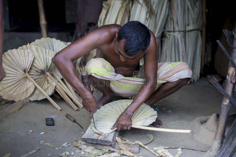 Een arbeider is bezig in het maken van hand - gehouden ventilator royalty-vrije stock afbeeldingen