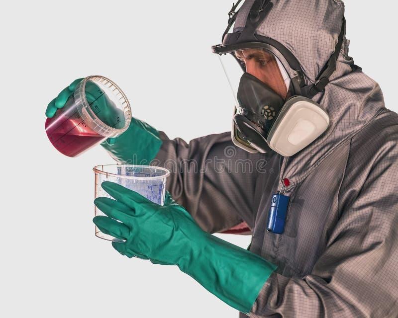 Een arbeider die beschermingsmiddel dragen giet rode vloeistof van één metend Kop aan een andere royalty-vrije stock foto
