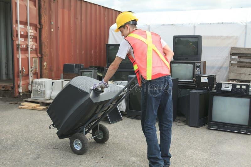 Een arbeider die recyclingsding op kringloopcentrum stock afbeeldingen