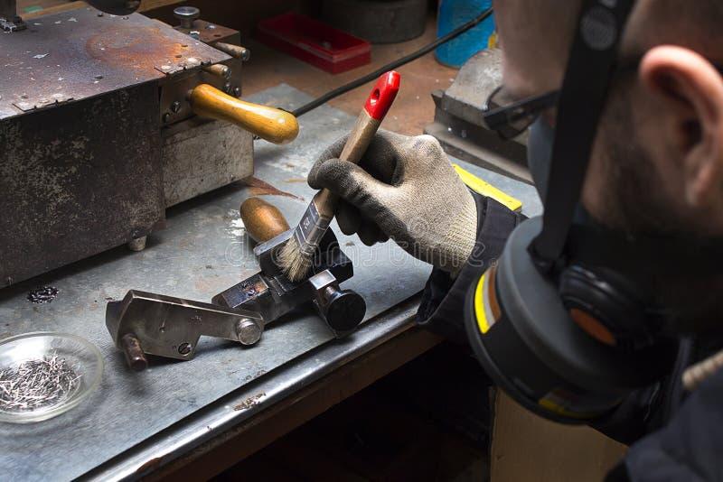 Een arbeider maakt de borstel die van de afgietselvorm een gasmasker en beschermende handschoenen dragen schoon stock afbeeldingen