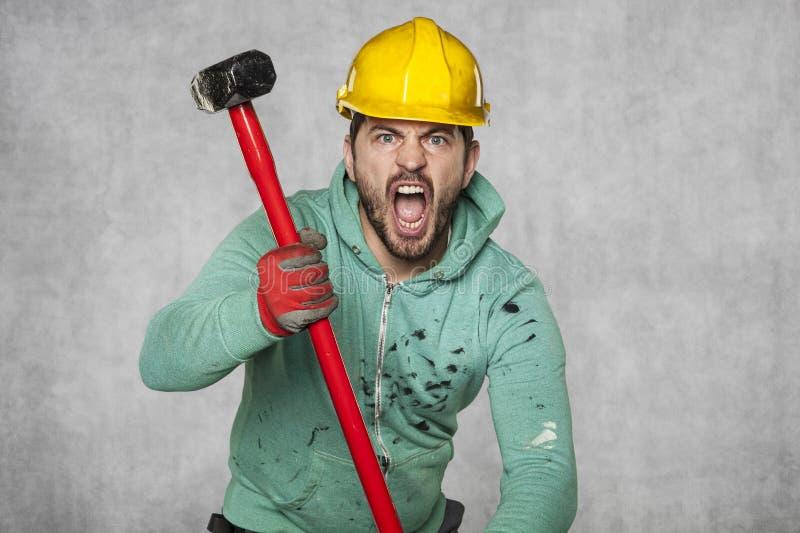 Een arbeider met een grote hamer gilt als een bezeten mens royalty-vrije stock foto