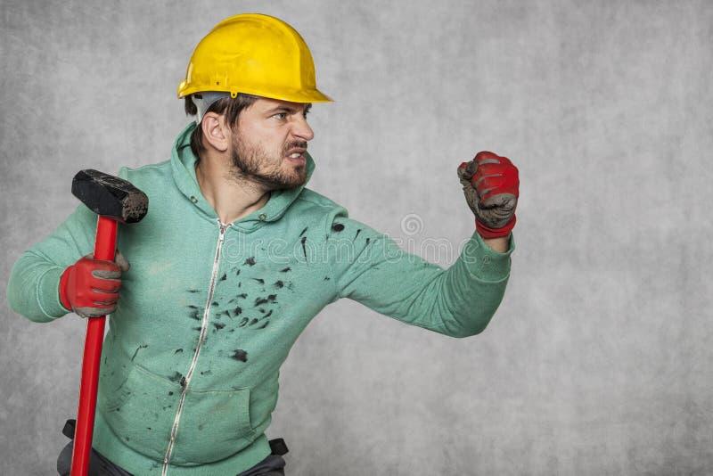 Een arbeider met een grote hamer, klaar voor de uitdaging stock fotografie