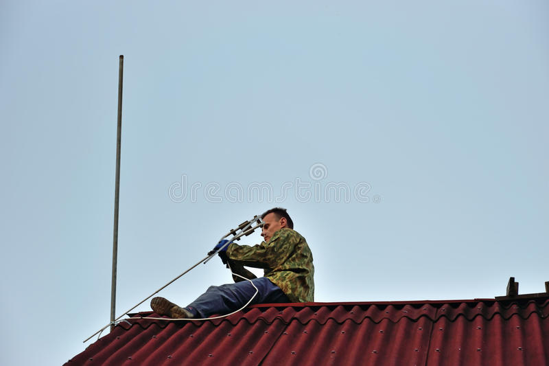 Een arbeider zet een individuele UHFtelevisieantenne op stock foto