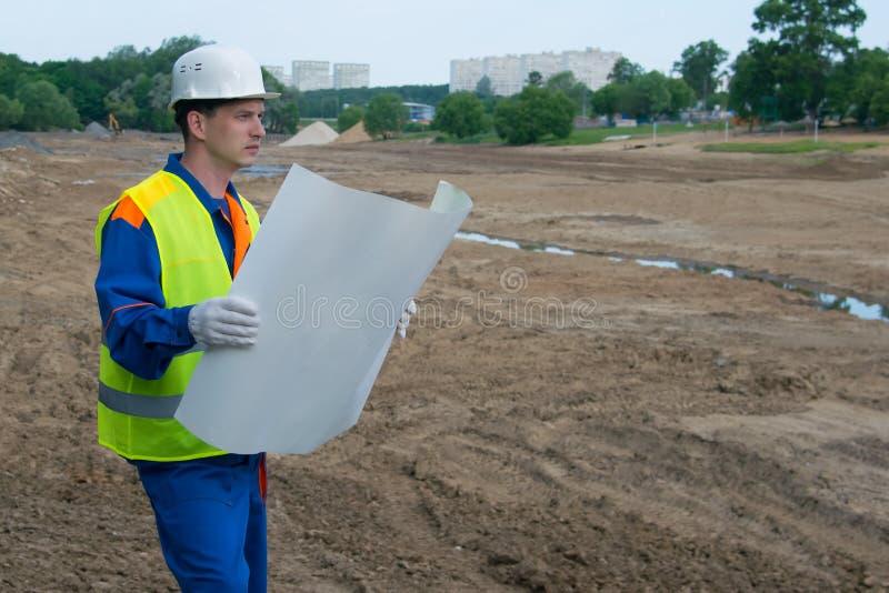 Een architect in een witte helm, die een tekening van een bouwproject bekijken, op een open gebied, voorbereide grond royalty-vrije stock foto