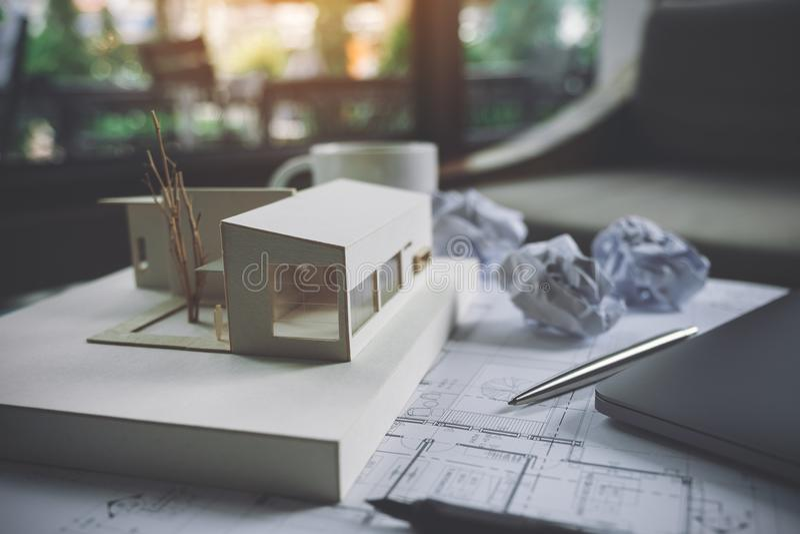 Een architectuurmodel met het document van de winkeltekening en laptop op lijst royalty-vrije stock fotografie