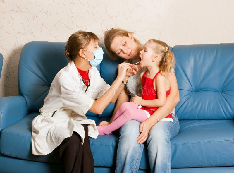 Een arts die een kind onderzoekt stock foto