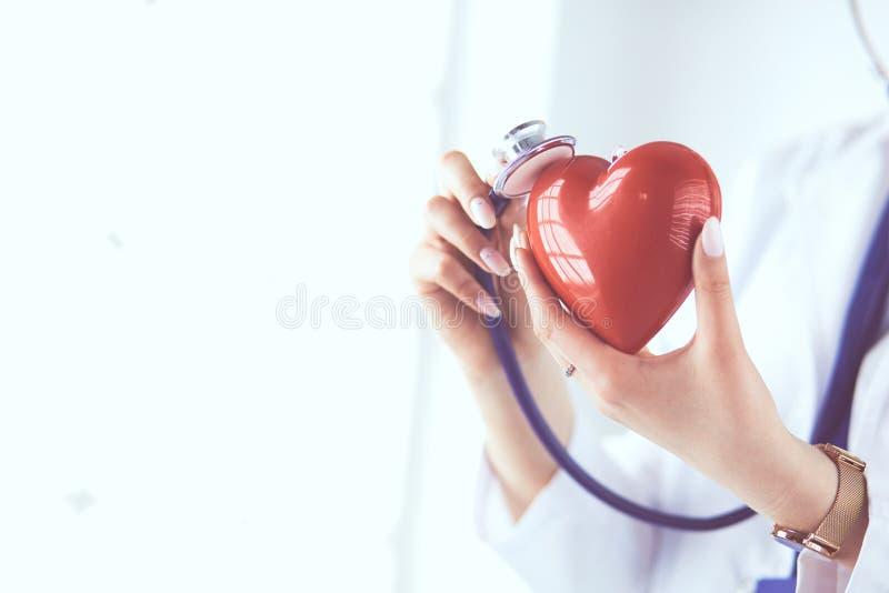 Een arts die met stethoscoop rood die hart onderzoeken, op witte achtergrond wordt geïsoleerd royalty-vrije stock afbeelding