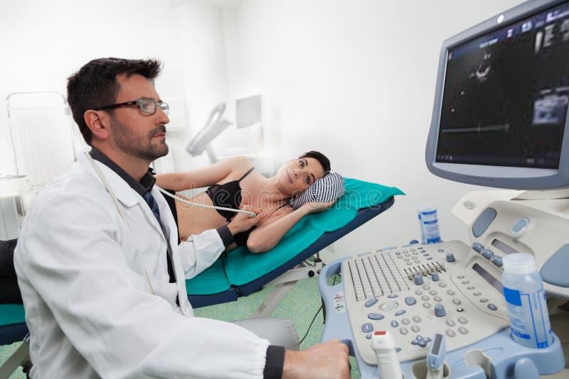 Een arts die zijn vrouwelijke patiënt met een ultrasone klankecography luisteren royalty-vrije stock fotografie