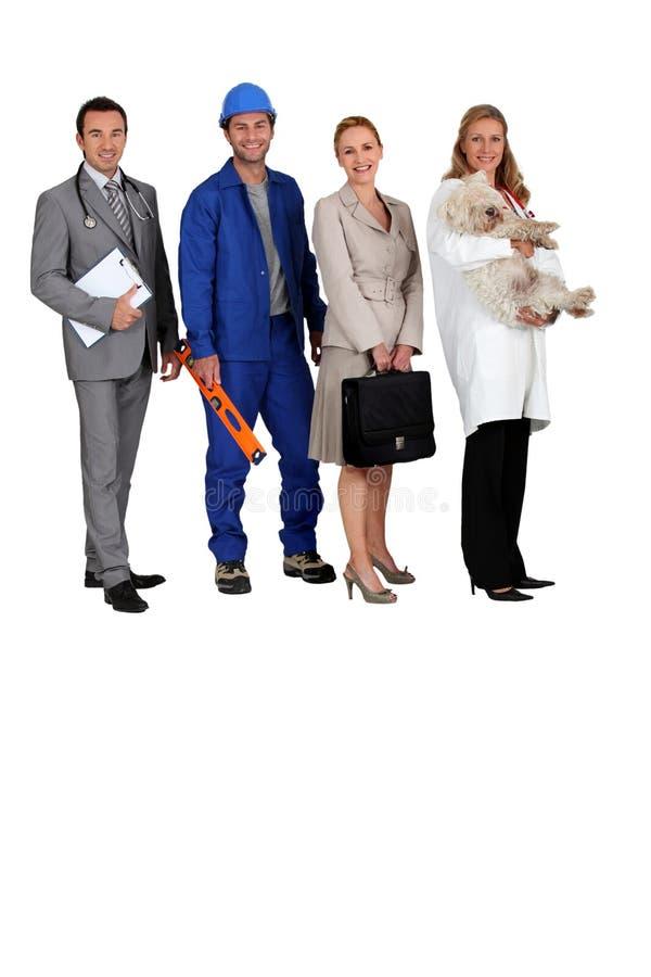 Een arts, een werkman, een bureauvrouw en een dierenarts stock foto