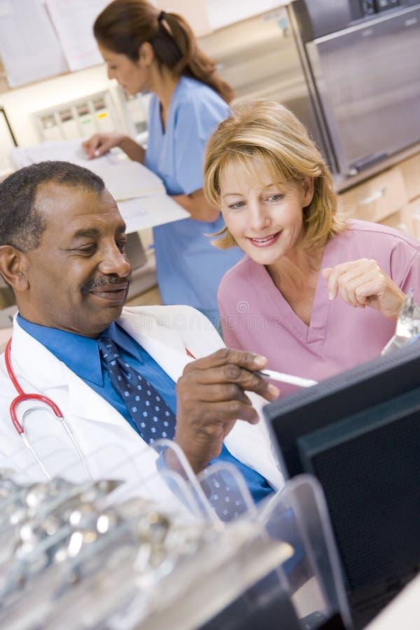 Een arts en een Verpleegster die iets bespreken