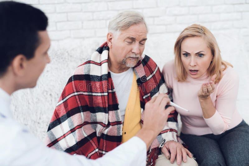 Een arts kwam aan de oude man in een gele cardigan De arts toont de thermometer, is de vrouw in schok stock afbeelding