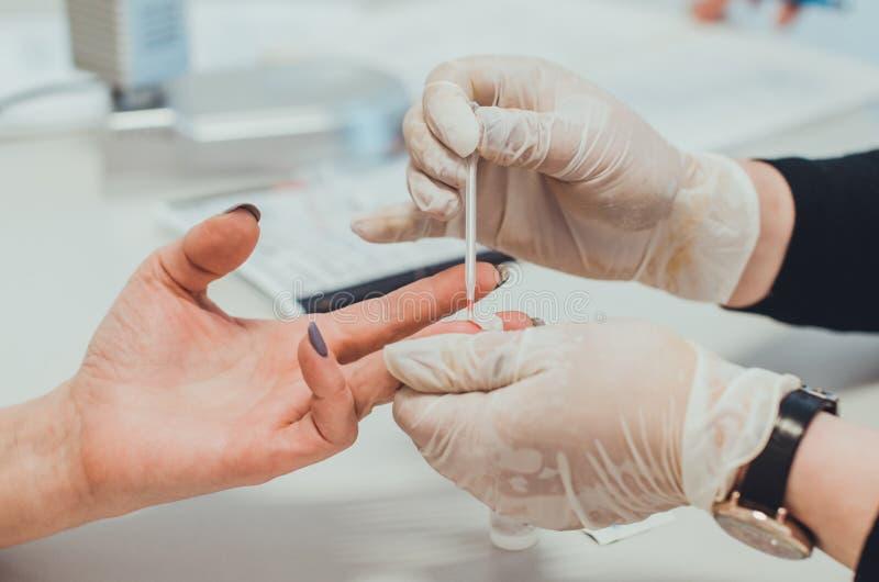 Een arts in medisch laboratorium die een bloedonderzoek met een pipetclose-up nemen stock fotografie