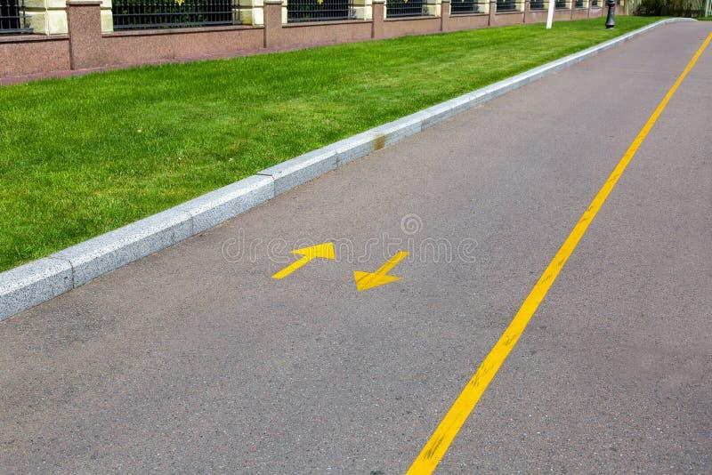 Een asfaltweg met gele noteringen en richtingpijlen stock afbeelding