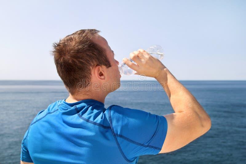 Een atleet die een onderbreking maken tijdens opleiding, drinkend vers schoon water van een fles, rust en geniet van de schone lu stock foto