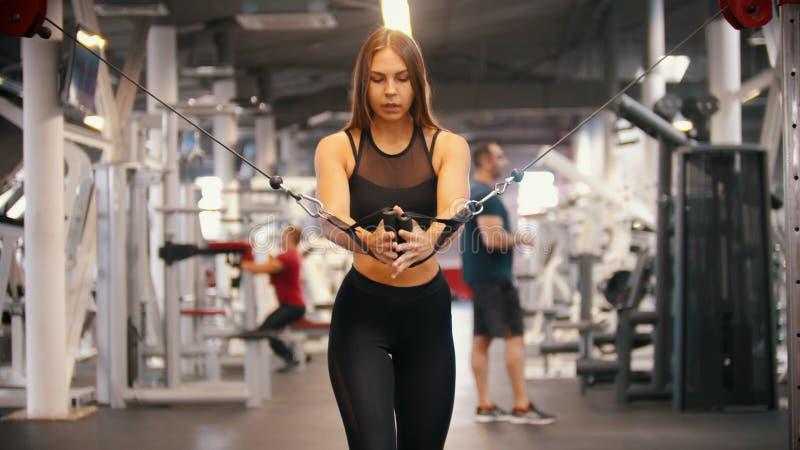 Een atletenvrouw die in de gymnastiek opleiden die - de handvatten trekken - opleidingshanden stock foto