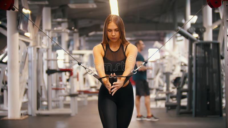 Een atletenvrouw die in de gymnastiek opleiden die - de handvatten trekken tegen zich - opleidingshanden stock foto
