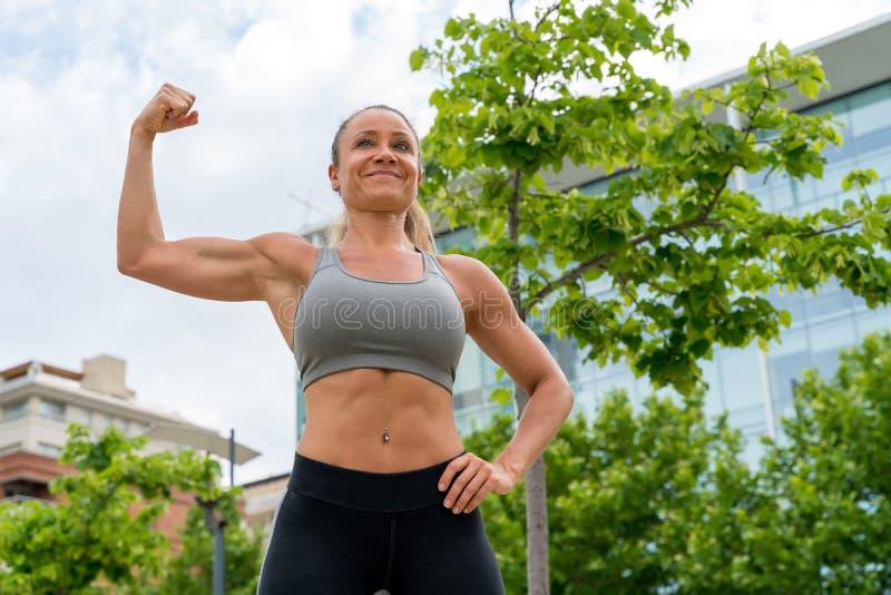 Een atletische vrouw in een grijze hoogste verbuiging in het park stock fotografie